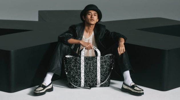 Posing with an oversized bag, Yudai Tateishi wears printed black and white loafers from the Jimmy Choo x Eric Haze collection.