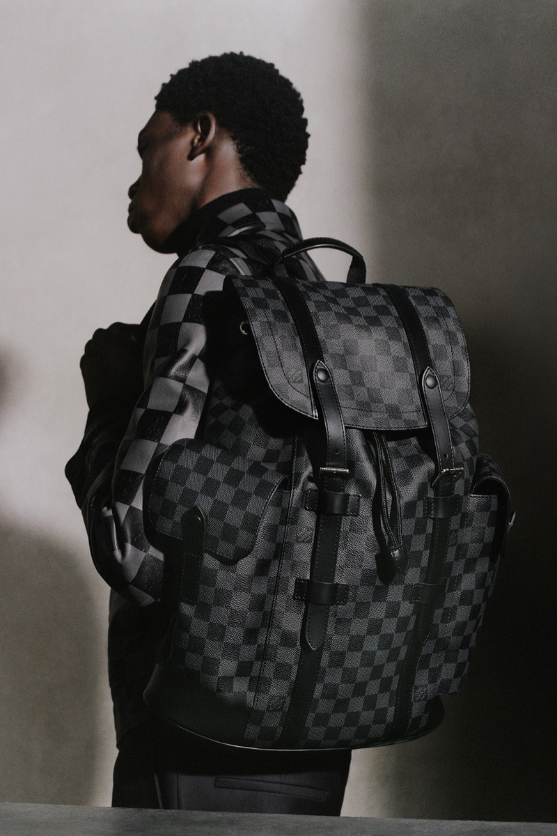 Embracing Louis Vuitton's Damier Graphite, Ottawa Kwami carries the brand's Christopher PM backpack.