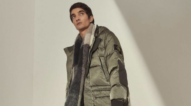 Bundling up for winter, Pablo Fernandez models a Stone Island nylon raso down-TC jacket with an Acne Studios alpaca-blend checked scarf, Bottega Veneta BV tire leather boots, and a Canada Goose sweater.